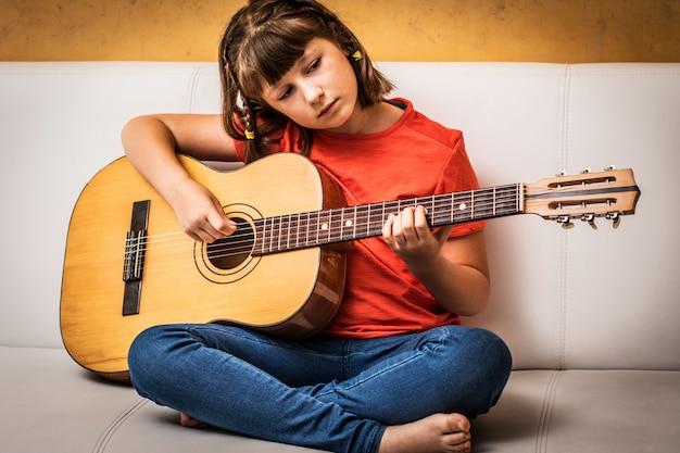 Het geconcentreerde meisje oefent met akoestische gitaar thuis zittend op bank