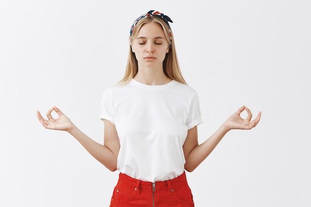 Het geduldige jonge blonde meisje stellen tegen de witte muur