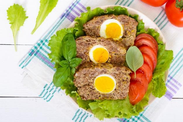 Het gehaktbrood vulde gekookt ei met verse tomaat en slabladeren op een plaat op een witte houten lijst. bovenaanzicht.