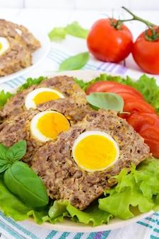 Het gehaktbrood vulde gekookt ei met verse tomaat en slabladeren op een plaat op een witte houten lijst. detailopname.