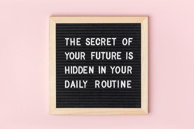 Het geheim van je toekomst zit verborgen in je dagelijkse routine. motiverende citaat op zwarte letter bord op roze achtergrond. concept inspirerende quote van de dag. wenskaart, briefkaart.