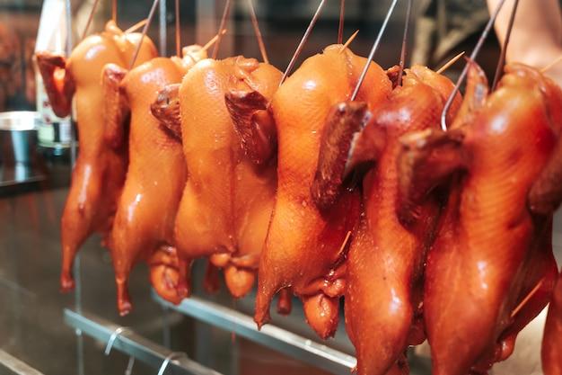 Het gehele geroosterde kip hangen bij restaurant