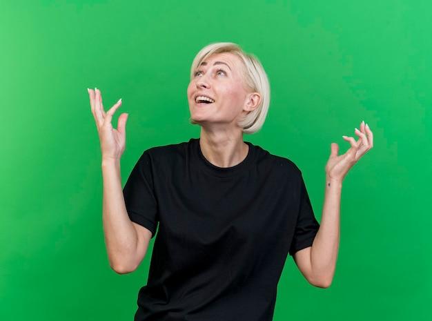 Het geïmponeerde blonde slavische vrouw van middelbare leeftijd houden dient de lucht in die omhoog geïsoleerd op groene muur kijkt