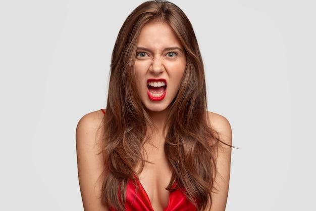 Het geïrriteerde glamourmeisje fronst gezicht en opent mond