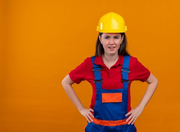 Het geïrriteerde jonge bouwersmeisje legt beide handen op taille op geïsoleerde oranje achtergrond met exemplaarruimte