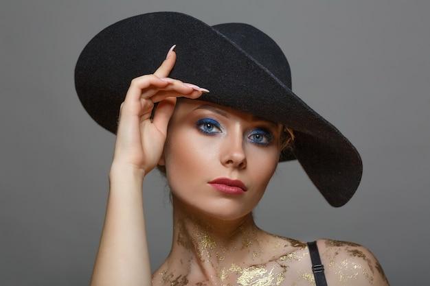 Het geïsoleerde portret van mooie vrouw met met maakt omhoog in zwarte hoed op wit ,.