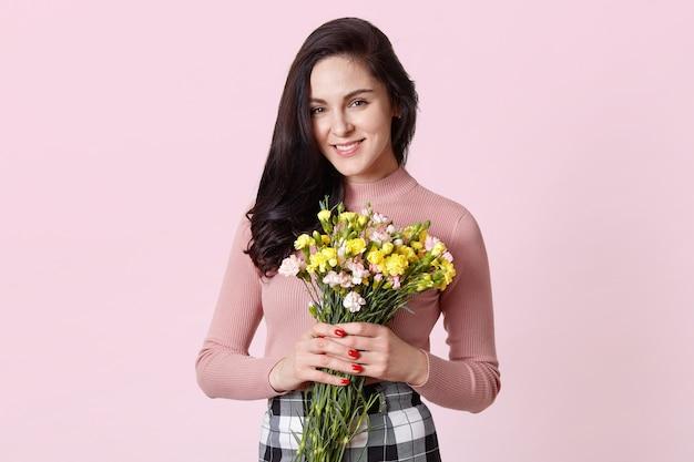 Het geïsoleerde schot van charmante leuke donkerharige vrouw draagt rooskleurig overhemd, zwart-wit geruite rok, houdt boeket van mooie bloemen