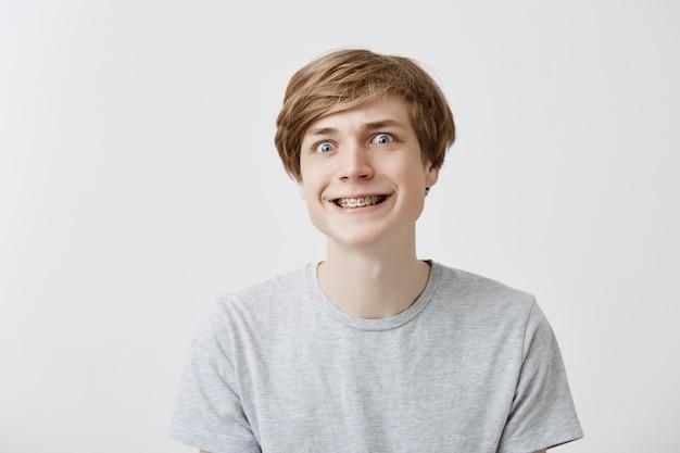 Het geïsoleerde schot van grappige jonge mens klemt tanden met steunen vast, makend gezichten, hebbend pret met vrienden. positieve blanke man met eerlijke haar grijns.
