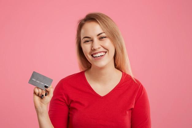 Het geïsoleerde schot van vrolijk wijfje houdt plastic kaart in handen, draagt rode sweater, gaat online aankopen doen, blij om geldbonus voor haar rekening te ontvangen, stelt op roze