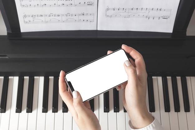 Het geïsoleerde smartphonescherm in vrouwelijke handen dichtbij de piano