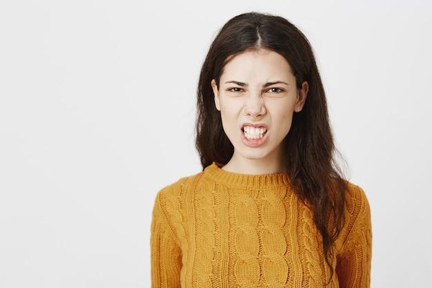 Het gekke en verontwaardigde grijnzende meisje balken vuisten en kijken met haat
