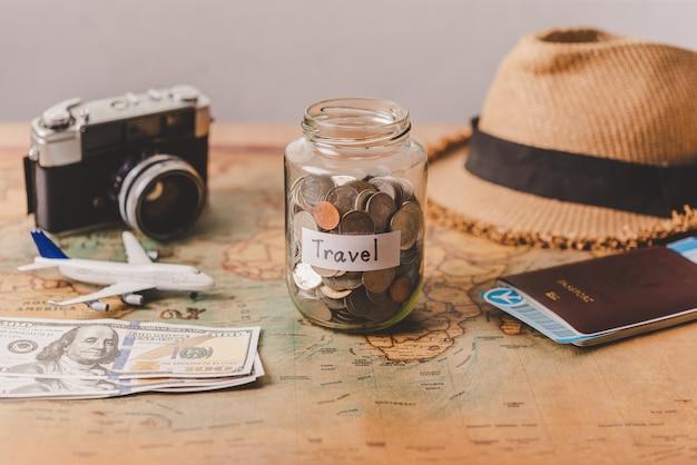 Het geld in de pot opgeslagen op de kaart, samen met een paspoort, concept om geld in te zamelen voor reizen.