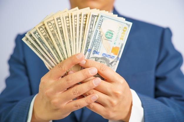 Het geld in de vs houdt op hand bedrijfsmens die een blauw kostuum draagt