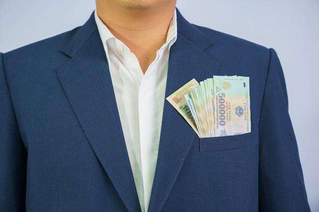 Het geld in vietnam houdt op hand bedrijfsmens die een blauw kostuum draagt