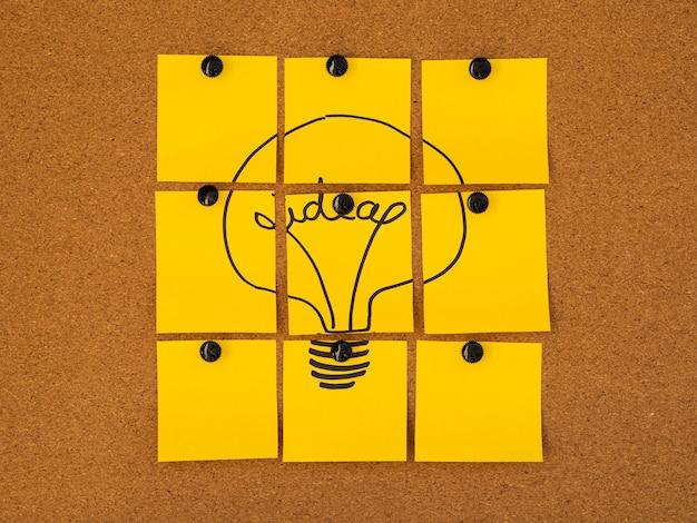 Het gele concept van het post-it gloeilampidee