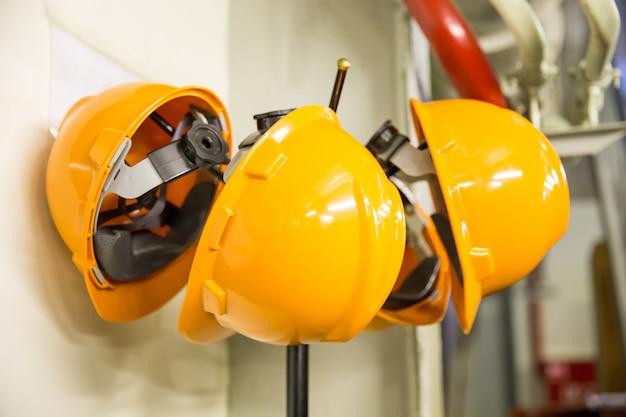 Het gele de slijtagehelm van de bouwvakkerveiligheid hangen op kapstok bij bouwwerf