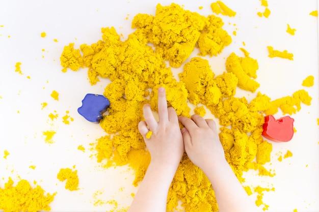 Het gele magische zand in jonge geitjes overhandigt dicht omhoog op een witte ruimte. vroeg zintuiglijk onderwijs. voorbereiden op school. ontwikkeling