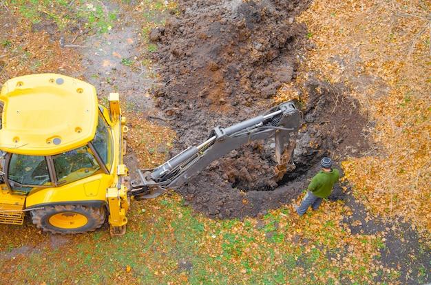 Het gele tractorgraafwerktuig graaft een kuil met een emmer, ongeval. doorbraak ondergronds. herfst winter bovenaanzicht