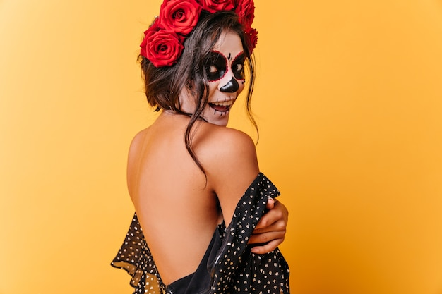 Het gelooide donkerharige meisje vormt gelukkig in jurk met open rug. dame met halloween-samenstelling verbaasd camera kijken.