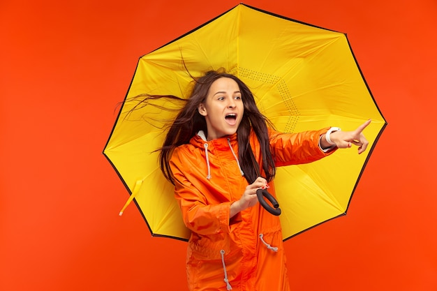 Het gelukkig lachende jonge meisje poseren in de studio in de herfst oranje jasje en wijst naar links geïsoleerd op rood.