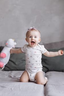 Het gelukkige aanbiddelijke meisje speelt thuis met stuk speelgoed eenhoorn op bed. concept van kinderdag. gelukkige baby's, familiedag