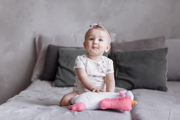 Het gelukkige aanbiddelijke meisje speelt thuis met stuk speelgoed eenhoorn op bed.