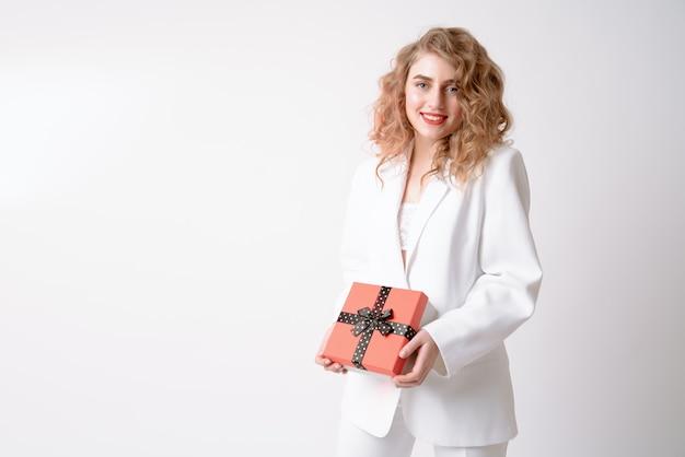 Het gelukkige aantrekkelijke krullende blondemeisje in wit kostuum houdt rood huidig doosportret