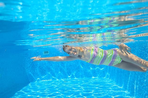 Het gelukkige actieve kind zwemt onderwater in pool