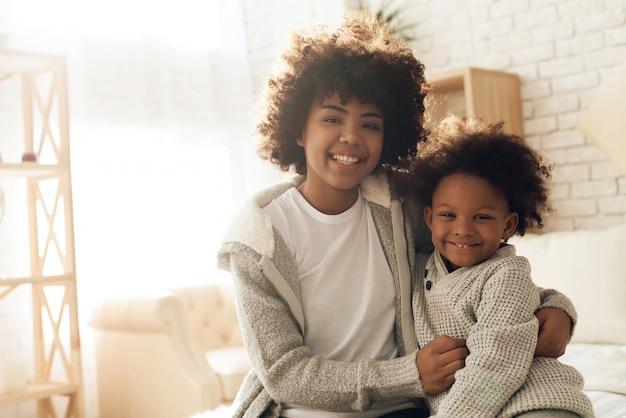 Het gelukkige afrikaanse amerikaanse moeder en dochter glimlachen.