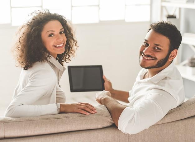 Het gelukkige amerikaanse paar afro gebruikt een digitale tablet.