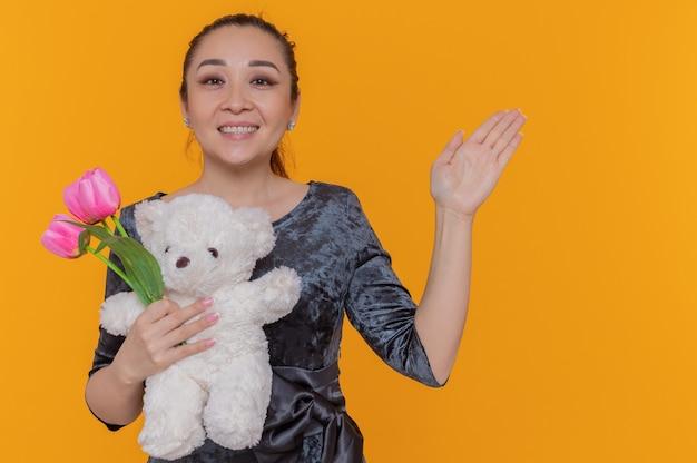 Het gelukkige aziatische boeket van de vrouwenholding van roze tulpen en teddybeer die vrolijk glimlachen viert de dag van de internationale vrouw die zich over oranje muur bevindt
