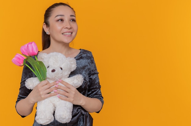 Het gelukkige aziatische boeket van de vrouwenholding van roze tulpen en teddybeer die vrolijk glimlachend opzij kijkt die internationale vrouwendag viert die zich over oranje muur bevindt