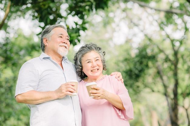 Het gelukkige aziatische hogere ouder paar drinkt samen koffie buiten in park