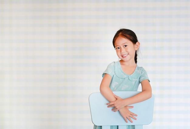 Het gelukkige aziatische kind peutermeisje in een kleuterschoolruimte stelt op plastic babystoel.