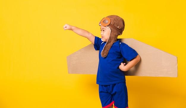 Het gelukkige aziatische kind weinig proefhoed van de jongensslijtage heft hand omhoog met stuk speelgoed de vleugels van het kartonnen vliegtuig op