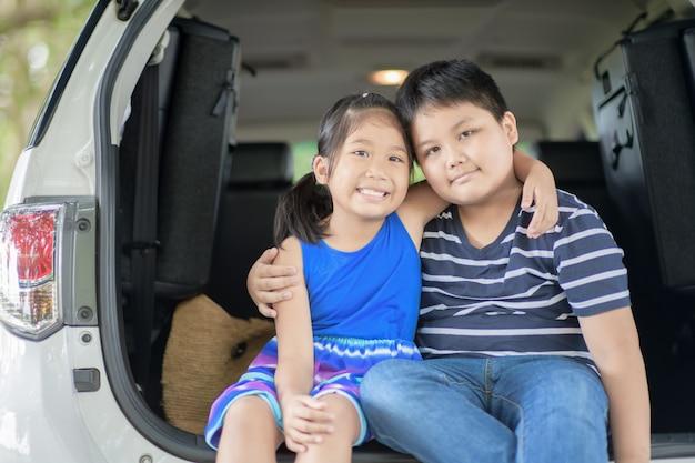 Het gelukkige aziatische kind zit in de auto,