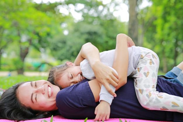 Het gelukkige aziatische mamma omhelst haar dochter liggend in het groene gazon