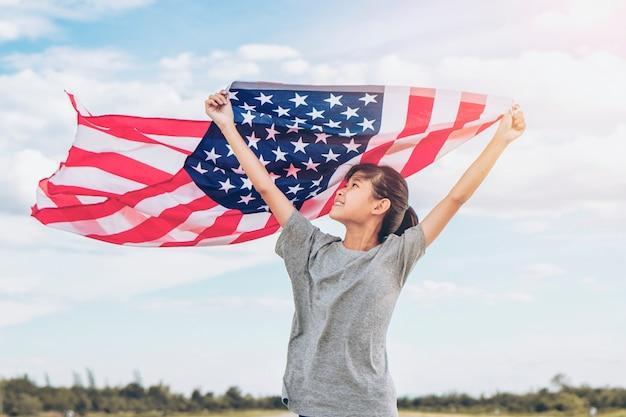 Het gelukkige aziatische meisje met amerikaanse vlag de vs viert van juli vieren