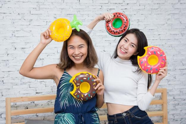 Het gelukkige aziatische meisje twee spelen met doughnutvlotter