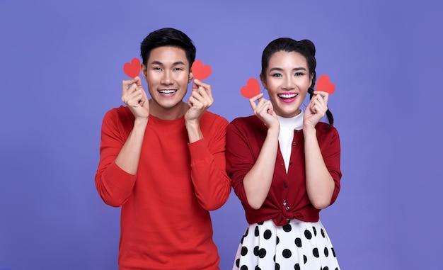 Het gelukkige aziatische paar houdt rode document harten en glimlacht op paars. valentijnsdag concept.