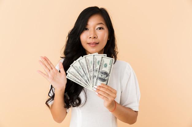 Het gelukkige aziatische vrouw stellen geïsoleerd over beige de holdingsgeld van de muurruimte.