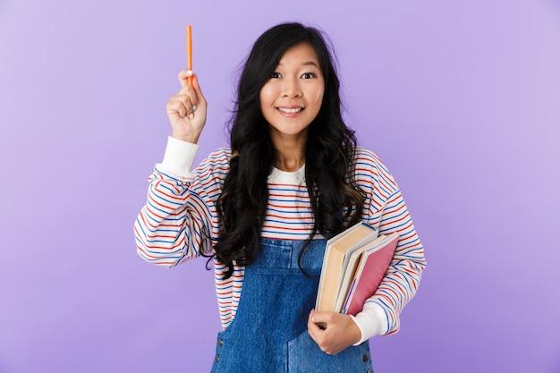 Het gelukkige aziatische vrouw stellen geïsoleerd over purpere boeken van de muurholding hebben een idee
