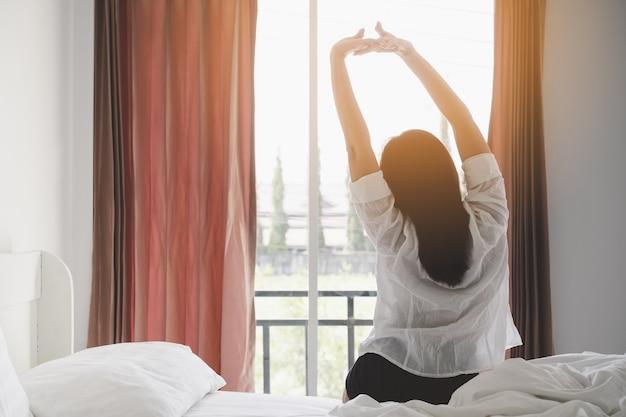 Het gelukkige aziatische vrouw uitrekken zich op bed na ontwaken bij ochtend in slaapkamer.
