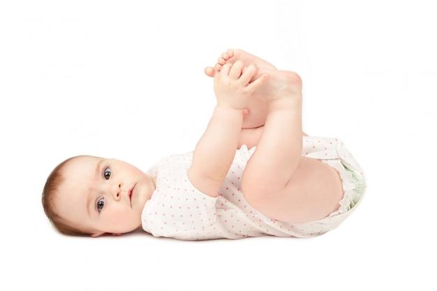 Het gelukkige baby spelen met zijn voeten die op witte achtergrond worden geïsoleerd.