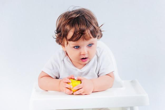 Het gelukkige babyjongen zitting en eten