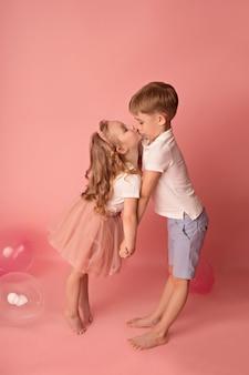Het gelukkige babymeisje en de jongen met ballons kussen.