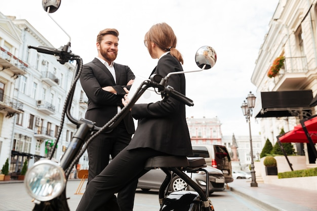 Het gelukkige bedrijfspaar stellen dichtbij de moderne motor in openlucht