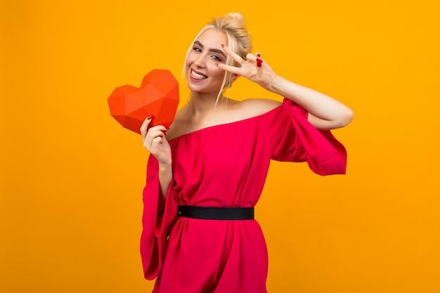 Het gelukkige blije glimlachende blondemeisje in rode kleding houdt rood document hart