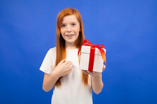 Het gelukkige blije tienermeisje met rood haar gelooft niet geluk houdend een giftdoosblauw