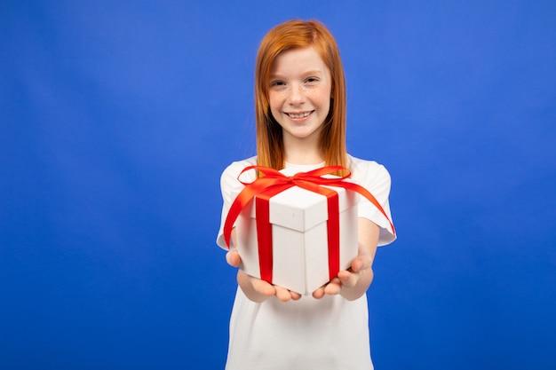 Het gelukkige blije tienermeisje met rood haar houdt een verjaardagsgeschenkblauw stand